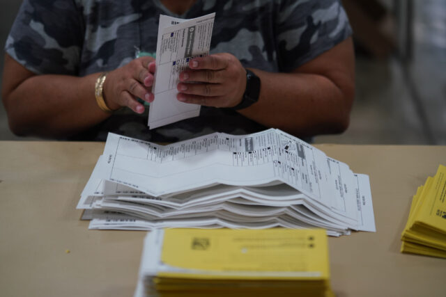 Workers remove ballots to ready for scanning process at the Hawaii Convention Center.