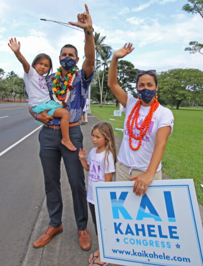 Kai Kahele, candidate for US congress, sign-waves with his wife Maria, daugthers Iolana (6) (standing) and Namaka (4) along Hilo's Bayfront area. Photo: Tim Wright