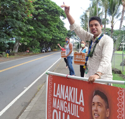 Lanakila Mangauil, candidate for Big Island OHA Trustee , sign-waves with supporters in Naalehu. Photo: Tim Wright
