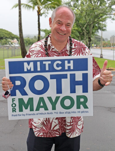 Mitch Roth candidate for Big Island Mayor holds up his sign outside of his Hilo campaign office. Photo: Tim Wright