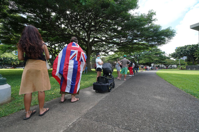 Waimanalo resident Mark Hartsock wears a Hawaiian flag while standing in a long line to vote in the 2020 General Election near Honolulu Hale.