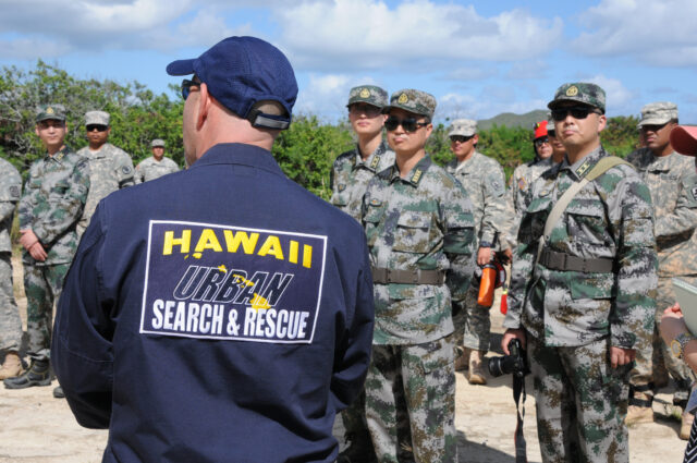 Gary Wiegand from the State Civil Defense K-9 Unit discusses search and recovery with members of the People's Liberation Army. Soldiers from United States Army Pacific, Hawaii Army National Guard and Army Corps of Engineers along with representatives from the Federal Emergency Management Agency will participate with the People's Liberation Army in a Academic Disaster Management Exchange. The 2013 DME is a U.S. Army hosted subject matter expert exchange focused on an international Humanitarian Assistance and Disaster Relief operation. Both U.S. and PLA demonstrate equipment used during HA/DR operations Nov. 14.