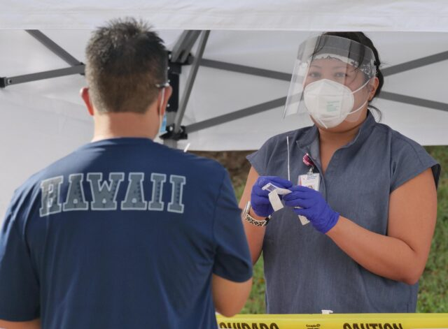 A medical technician demonstrates how to administer a COVID-19 test during a free testing clinic at the Waikiki Shell, in Honolulu, HI, Wednesday, November 11, 2020. (Ronen Zilberman photo Civil Beat)