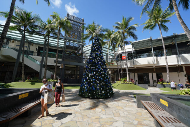Masked customers stroll by the holiday decorations at Ala Moana Center during COVID-19 pandemic.