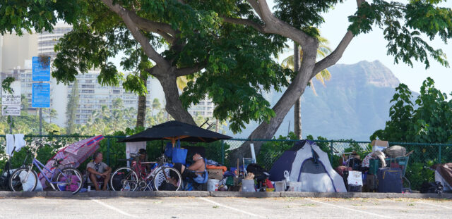 People in tents camp along fence of the Hilton Lagoon in Waikiki during COVID-19 pandemic. November 12, 2020