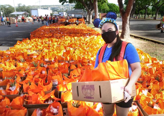 """Volunteer Crystal Siruno holds a box of bagged food to be distributed to 2500 Hawai'i residents arriving to Aloha Stadium Monday, November 16, 2020. Crystal said she wore her speical Mickey Mouse ears headband to """"help spread a little magic"""" around the free pop-up food distribution event orgnanized by the Hawai'i Foodbank."""