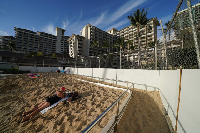 Lone sunbather fronting the fenced Halekulani Hotel during COVID-19 pandemic.