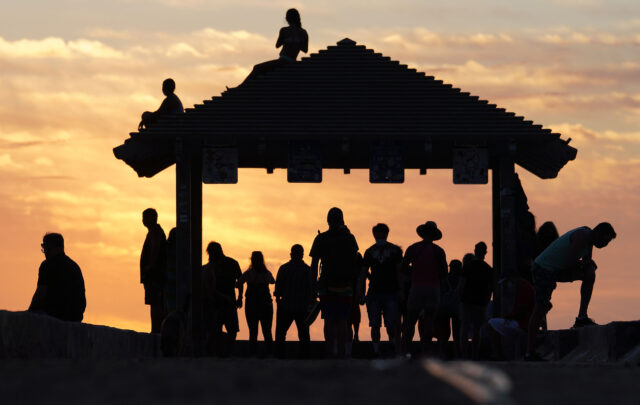 Silhouette of locals and visitors at the gazebo located at 'Walls' as they enjoy a beautiful sunset during COVID-19 pandemic.