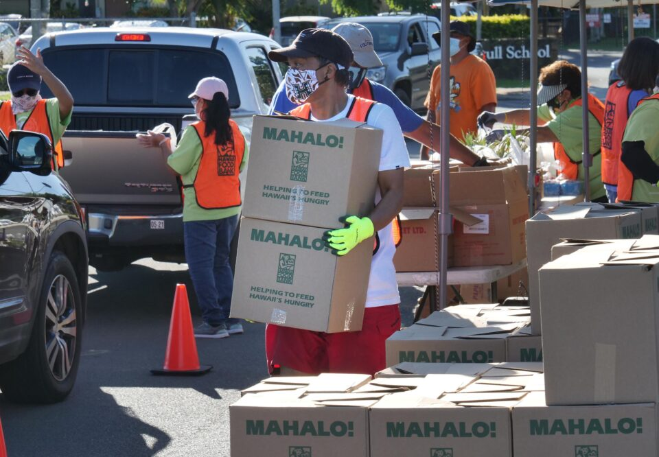 Hawai'i Foodbank volunteer, Jon Fernandez, carries boxes to be loaded into waiting vehicles during a pop-up food distribution event at the 'Ewa Pu'uloa District Park, Wednesday, December 2, 2020. (Ronen Zilberman Civil Beat)