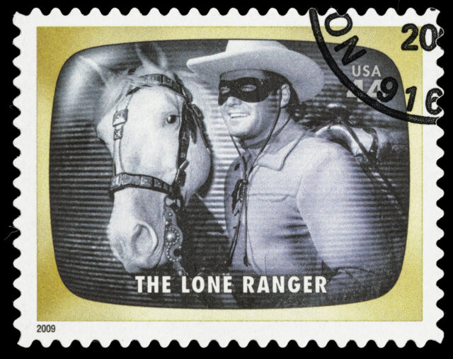 """Sacramento, California, USA - June 8, 2012: A 2009 USA postage stamp with a photo of Clayton Moore as the title character of the classic 1949-1957 TV Western drama series, The Lone Ranger. Moore is standing next to his character's white stallion, Silver."""