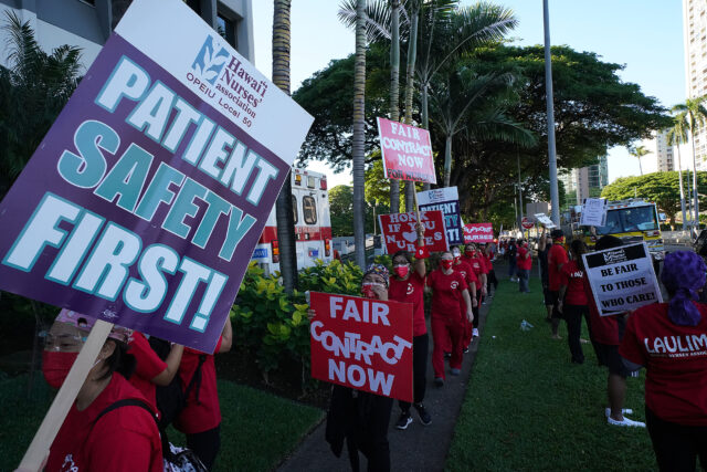 Nurse hold signs protesting fronting the Kapiolani Womens and Childrens hospital.
