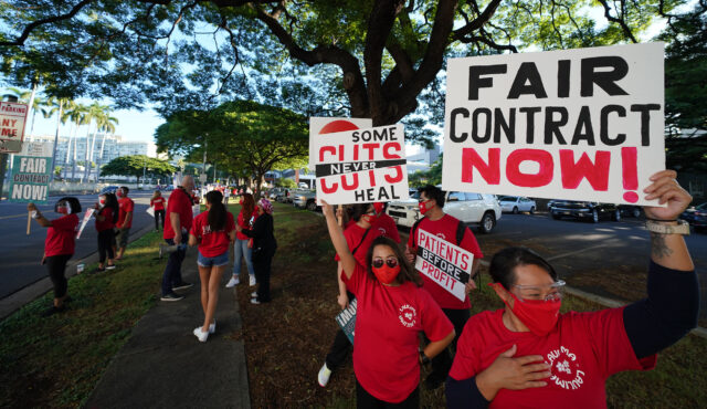 Nurse hold signs protesting at Punahou street near Kapiolani Womens and Childrens hospital.