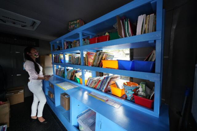 Amy Truong stands inside the Hawaii Literacy Bookmobile with books on shelves.