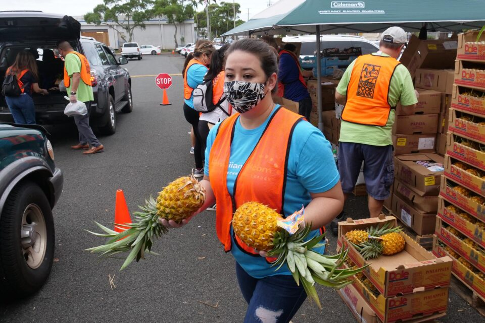 Hawai'i Foodbank volunteer, Natane Thompson, carries pineapples to load into waiting cars during a pop-up food distribution event at Kahihi District Park on Wednesday, December 9, 2020. (Ronen Zilberman photo Civil Beat)