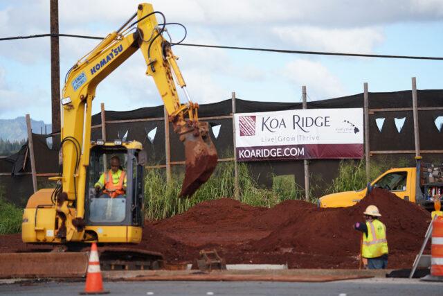 Workers on Ka Uka Boulevard with Koa Ridge development banner in background.