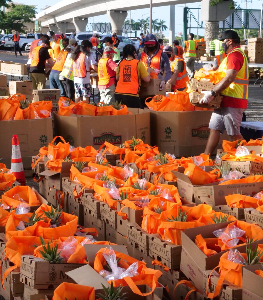 Volunteers pack boxes of food for the last mass distribution event of the year at Aloha Stadium sponsored by the City of Honolulu and the Hawai'i Food Bank, on Friday, December 18, 2020. (Ronen Zilberman photo Civil Beat)