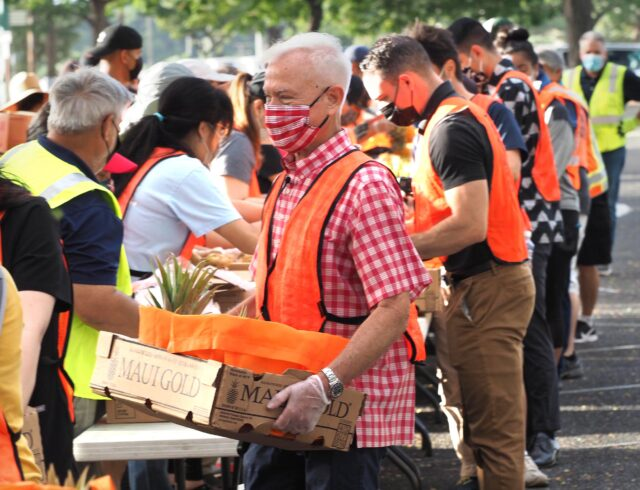 Honolulu Mayor Kirk Caldwell works with other volunteers pack boxes of food for the last mass distribution event of the year at Aloha Stadium sponsored by the City of Honolulu and the Hawai'i Food Bank, on Friday, December 18, 2020. (Ronen Zilberman photo Civil Beat)