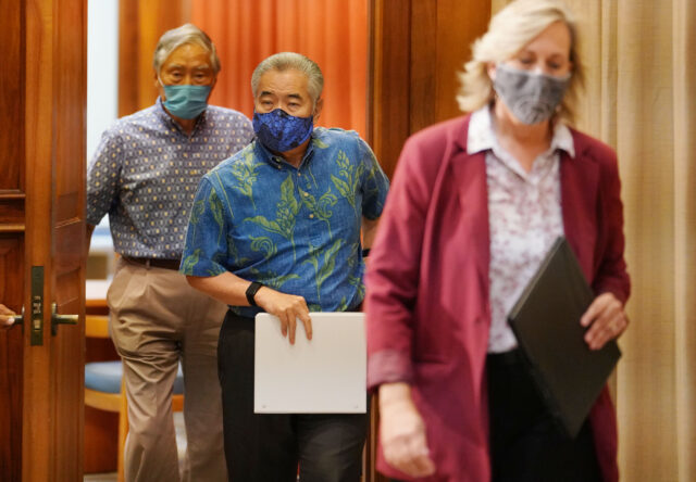 Governor David Ige walks into his ceremonial office before the budget press conference with his team.