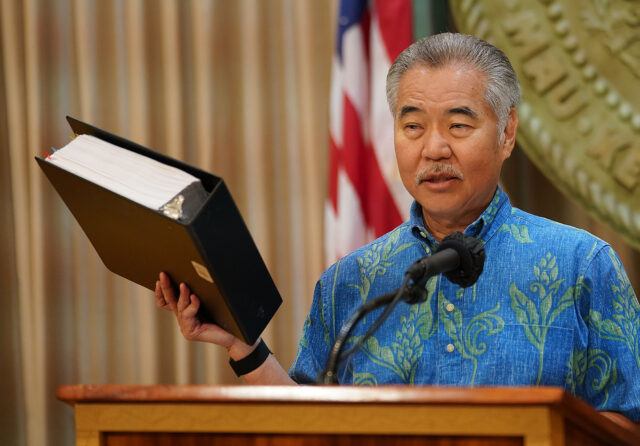 Governor David Ige holds the 6000 plus page congress stimulus draft during the governor's press conference announcing his balancing/cutting budget press conference held at the Capitol. December 21, 2020