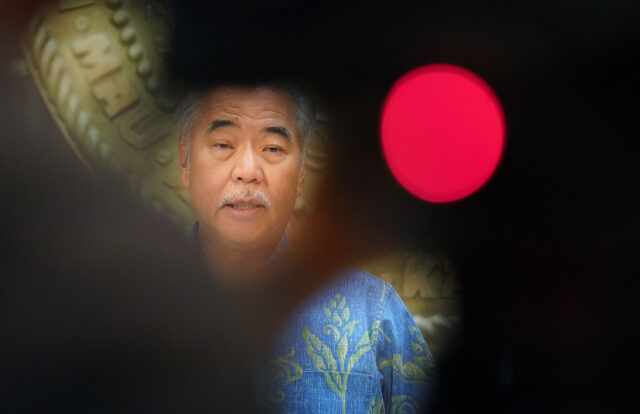 Governor David Ige seen with pool video photographer silhouette in the foreground discusses possible cuts to the state's budget during COVID-19 pandemic. December 21, 2020