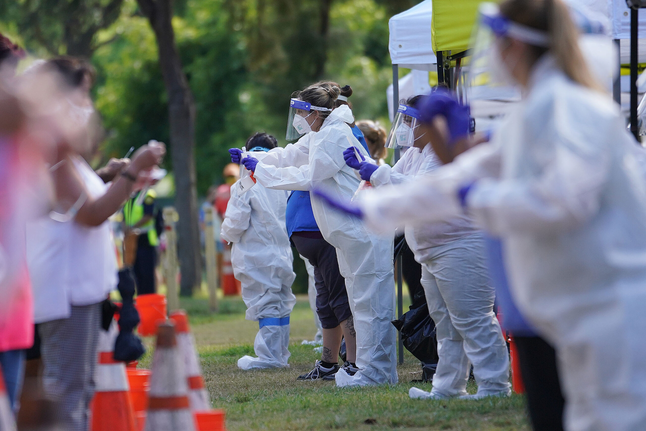 <p>Medical personnel helped with self-swab tests during a COVID-19 case surge in late summer. Hawaii's single-day case count hit a high of 355 in August, prompting another round of emergency regulations.</p>