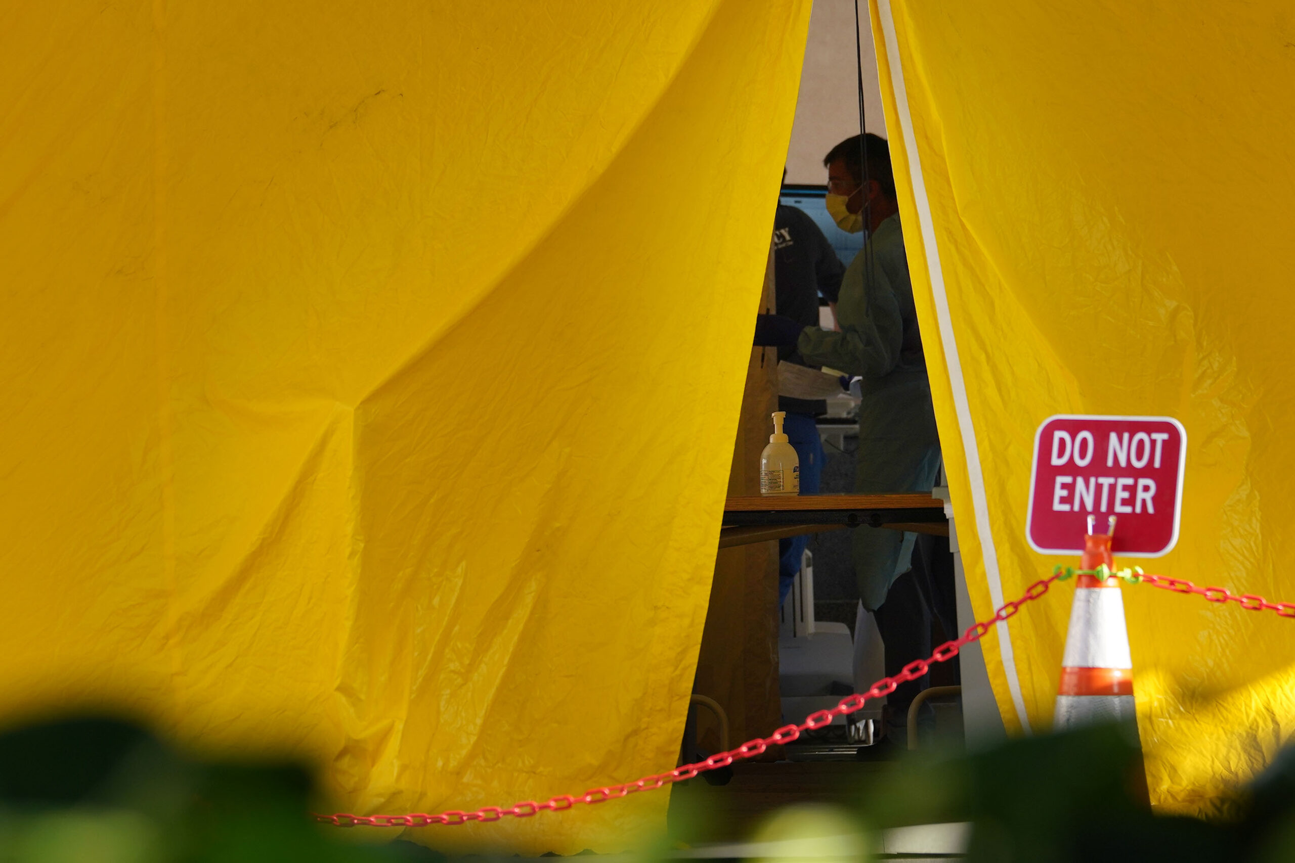 <p>By mid-March, hospitals began to prepare for a surge of COVID-19 cases that didn't quite arrive. Here a staff member at The Queen's Medical Center works inside a tent outside the emergency room on Punchbowl Street.</p>