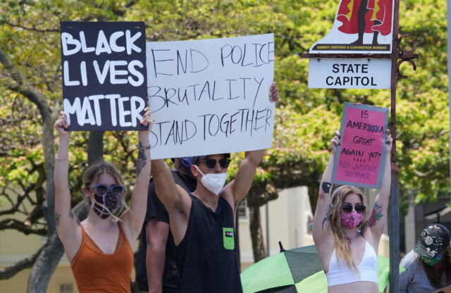 Black Lives Matter supporters hold signs along Beretania Street fronting the Capitol.