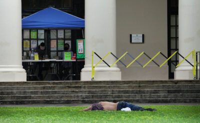 Person sleeps on the front lawn of the Hawaii State Library. January 5, 2021
