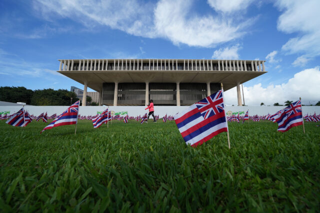 Hawaii State flags blow in the wind on opening day of the 2021 legislature.