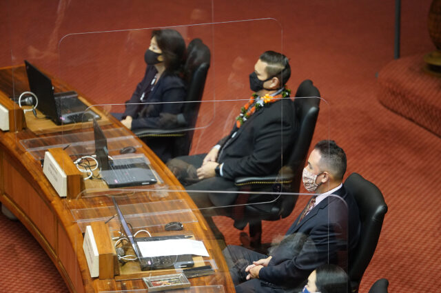 Masked and plexiglass partitioned House members listen to Speaker Saiki's speech that was postponed due to opening day security concerns. February 2, 2021