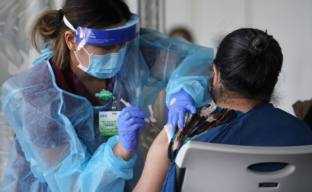 Registered Nurse Alexis Lagasca from Kalihi Palama Health Center gives COVID-19 vaccinations at St. Elizabeth Church.