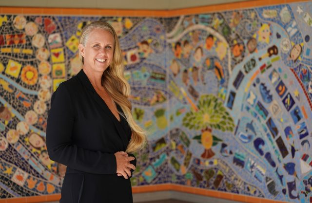 Hanahauoli School teacher Amber Makaiau stands fronting a mosaic wall installation that the students created.