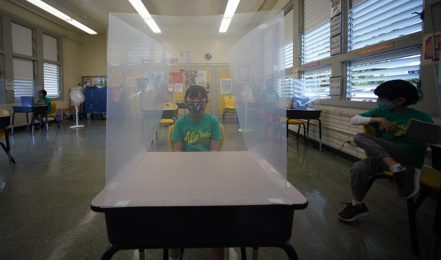 Ala Wai Elementary School student 3rd grader Azurae Sildora sits behind her plastic barrier during COVID-19 pandemic.