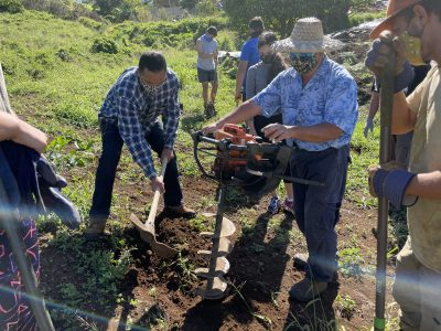 George Kahumoku uses a power tool to dig a hole while another volunteer assists with a pickax.