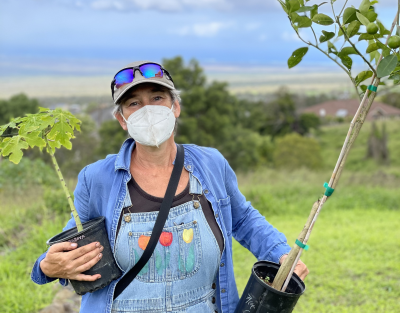 A woman in a mask and overalls holds two saplings.