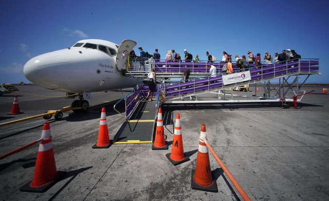 Passengers walk up ramp to board a Hawaiian Airlines flight bound to Honolulu.