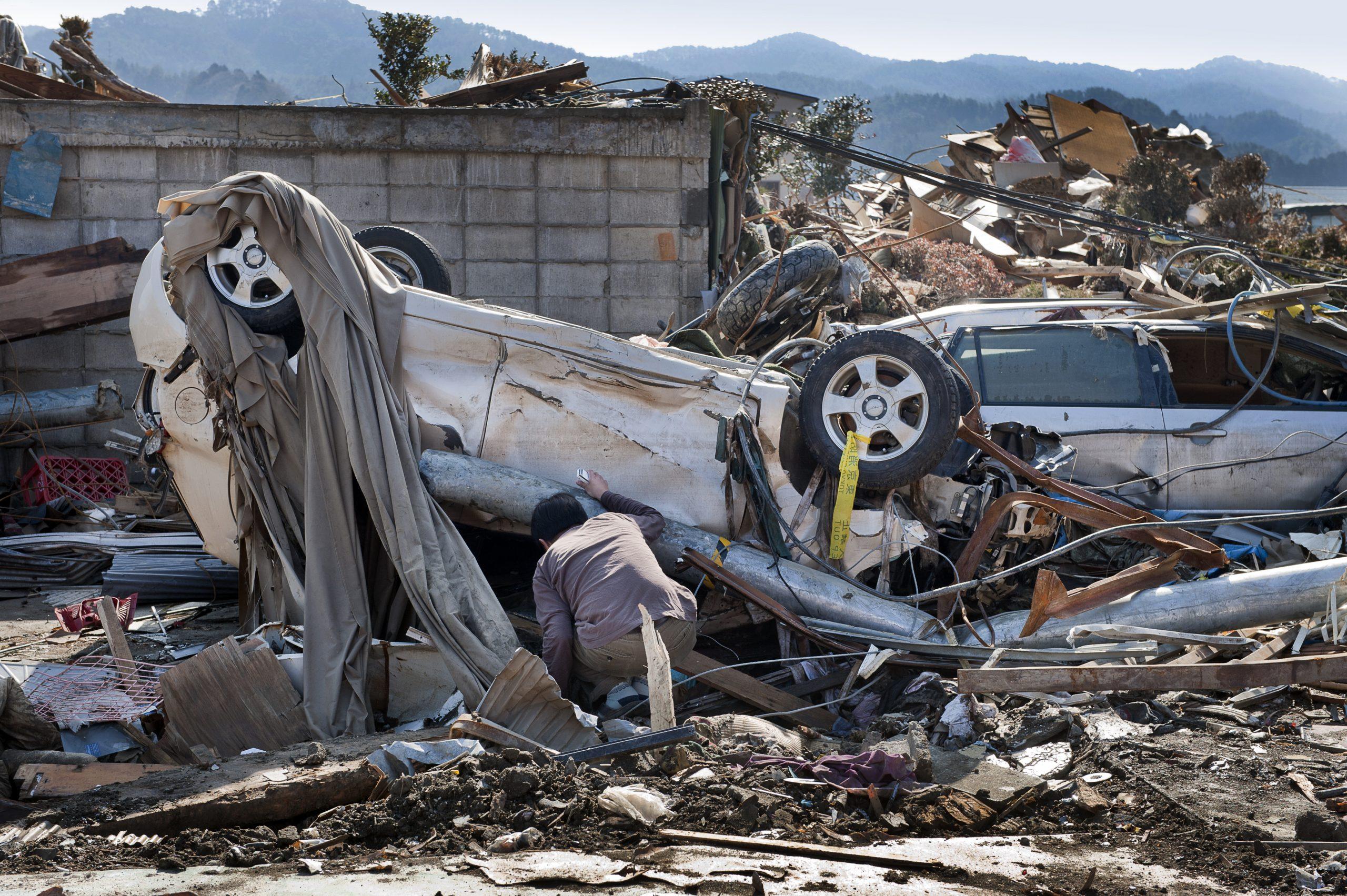 <p>A man searches through the rubble in Rikuzentakata in the wake of the tsunami.</p>