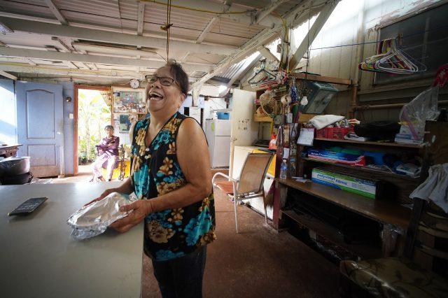 Kunia Village resident Tassie Fagarang smiles as she wraps some fried potatoes in her garage.