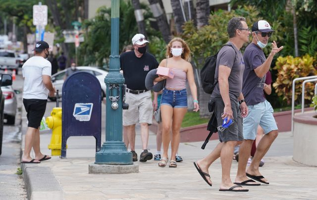 Masked and unmasked visitors stroll along Kalakaua Avenue as more visitors arrive. Saturdays arrivals topped almost 25,000 people. March 24, 2021