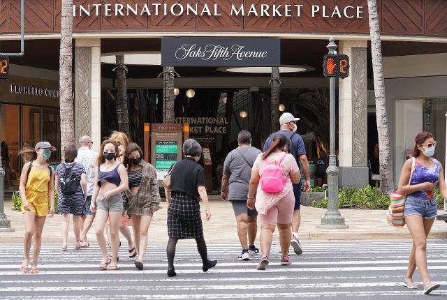 VIsitors cross Kalakaua Avenue fronting the International Marketplace in Waikiki.