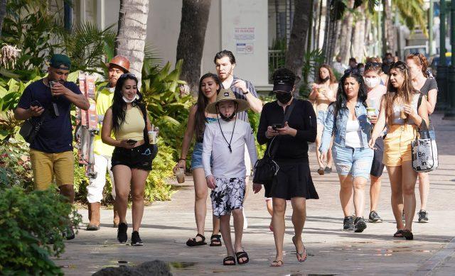 Unmasked visitors walk along Kalakaua Avenue during the COVID-19 pandemic.