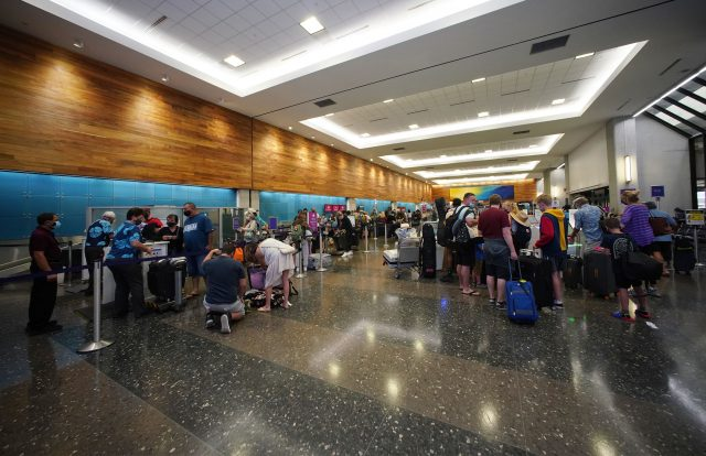 Scores of travelers check into interisland and domestic US flights at the Hawaiian Airlines check in area located at the Daniel K. Inouye International Airport during the COVID-19 pandemic.
