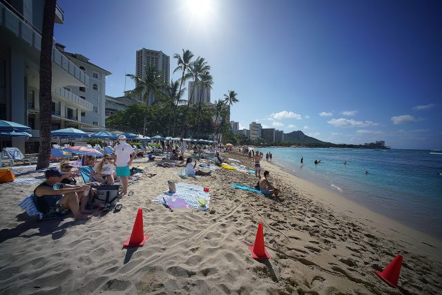Visitors lounge on the shores of Waikiki Beach during the COVID-19 pandemic.