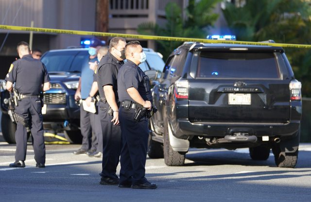Honolulu Police officers stand at shooting scene at the intersection of Philip Street and Kalakaua Avenue. April 5, 2021