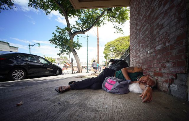 Person sleeps at the entrance to the parking at Chinatown's Smith Beretania Parking structure.