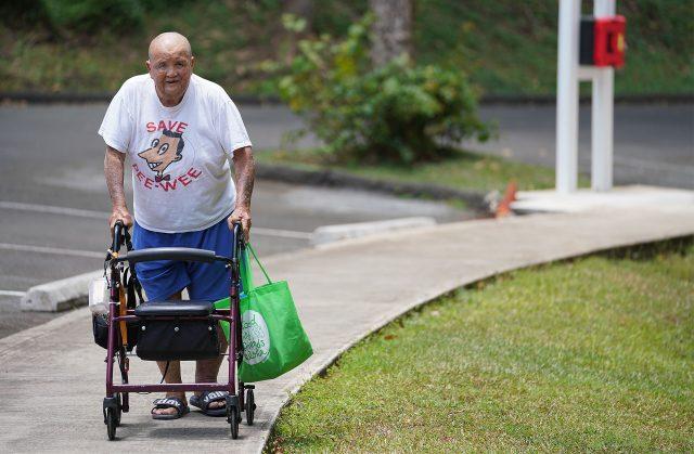 Dignity Senior Living at Oceanside Hawaii resident Lawrence Kawaguchi walks on sidewalk.