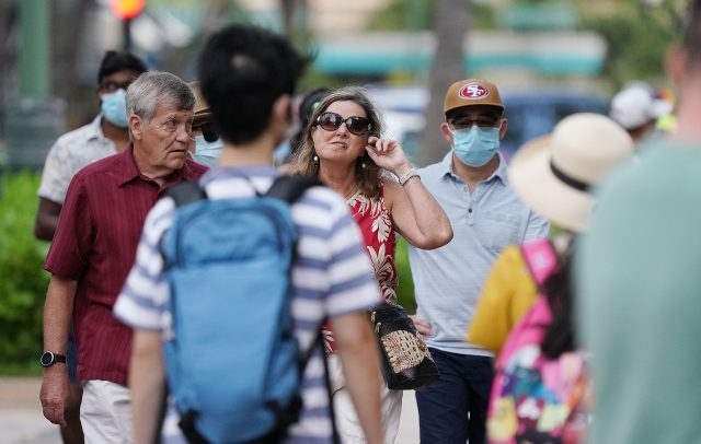 Visitors stroll along Kalakaua Avenue without their masks during the COVID-19 pandemic. April 27, 2021