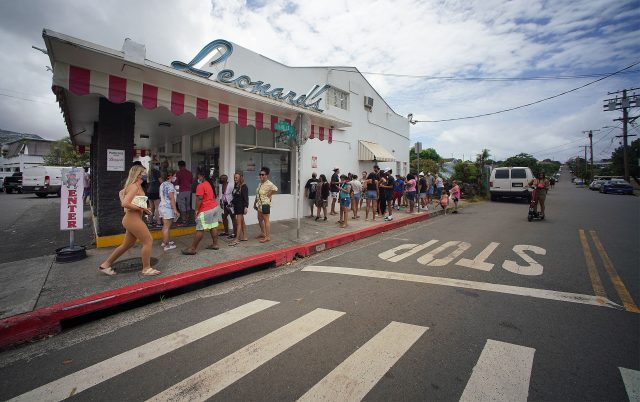 Line of customers goes out the door and around the side of Leonard's Bakery, a popular tourist spot for delectable Malasada treats.