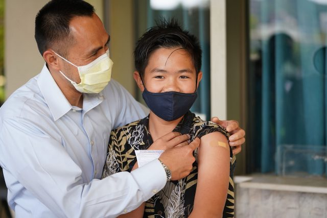 12-year-old Everett Pham with his father Julius Pham after Everett received the Pfizer COVID-19 vaccine at the Blaisdell Concert Hall.