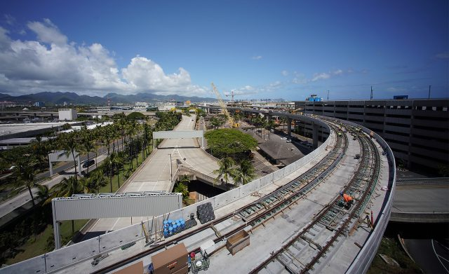 Workers assist in track installation on the rail guideway located at the Daniel K. Inouye International Airport.